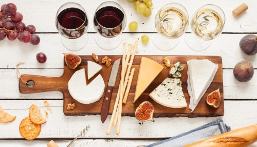 red-and-white-wine-plus-different-kinds-of-cheeses-cheeseboard-on-rustic-wooden-table