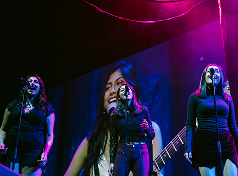 Three female vocalists smiling and singing