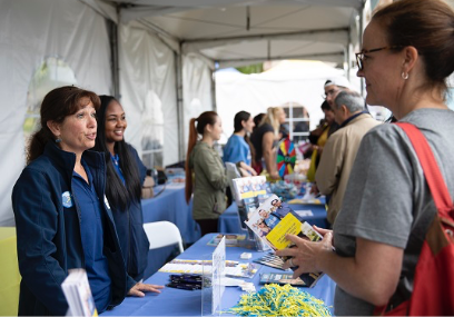 Parent & Family Association staff and volunteers answering a parent's question at an information booth during an event.