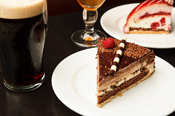 A delicious piece of pie or cake served with a cold glass of dark beer.